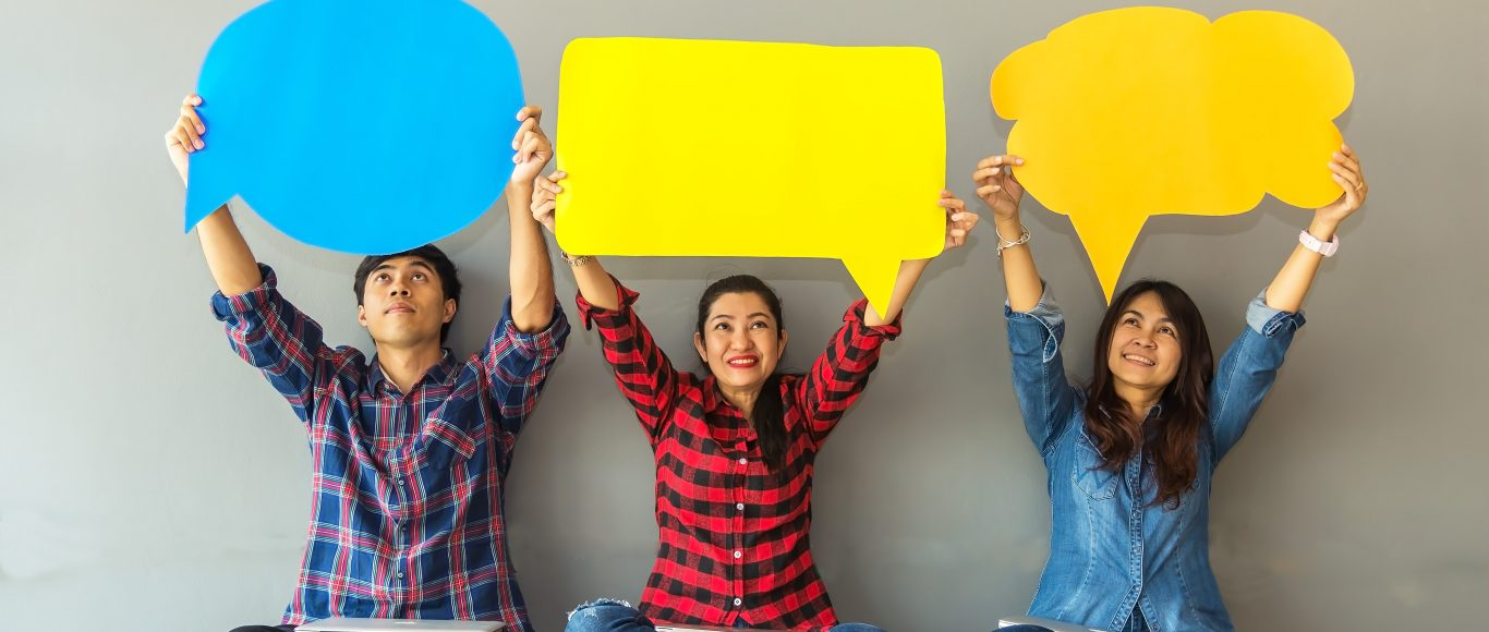 Photo of three people holding up speech and though bubbles
