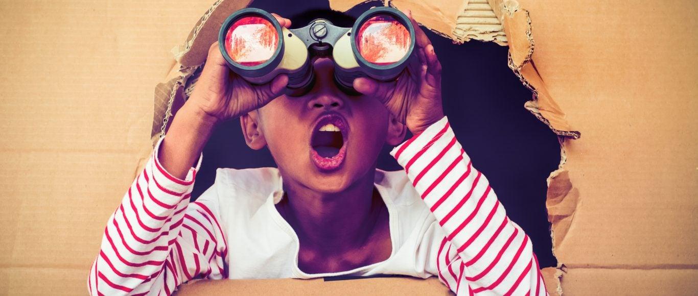 Photo of a young girl looking through binoculars