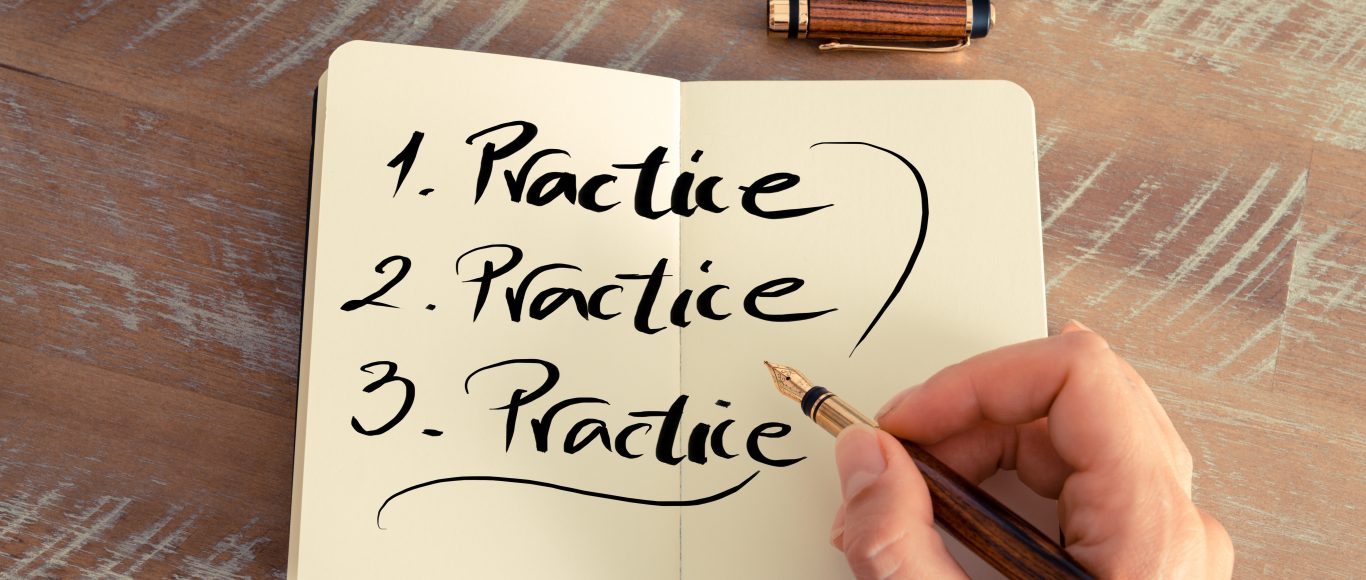 Photo of a notebook with the word 'practice' written 3 times