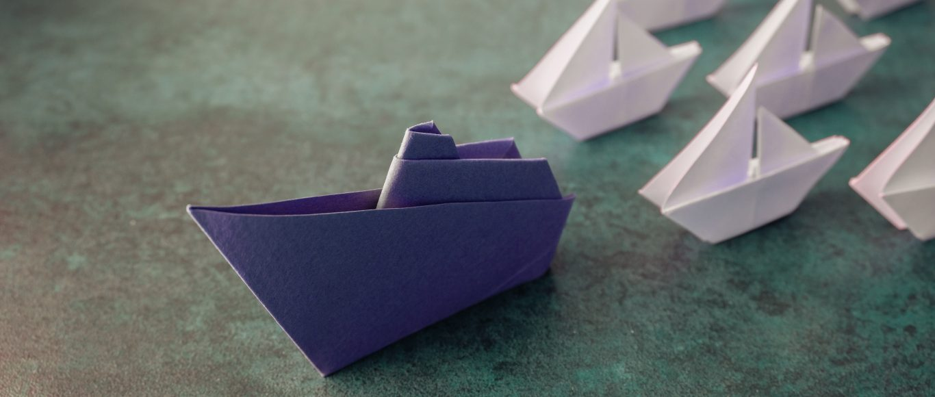 Photo of a blue paper boat leading other white ones