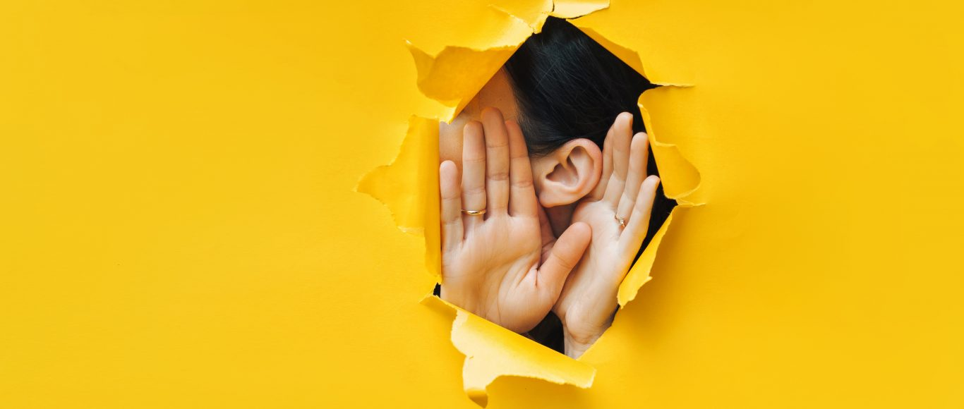 Photo of someone with their hands to their ears to mimic listening
