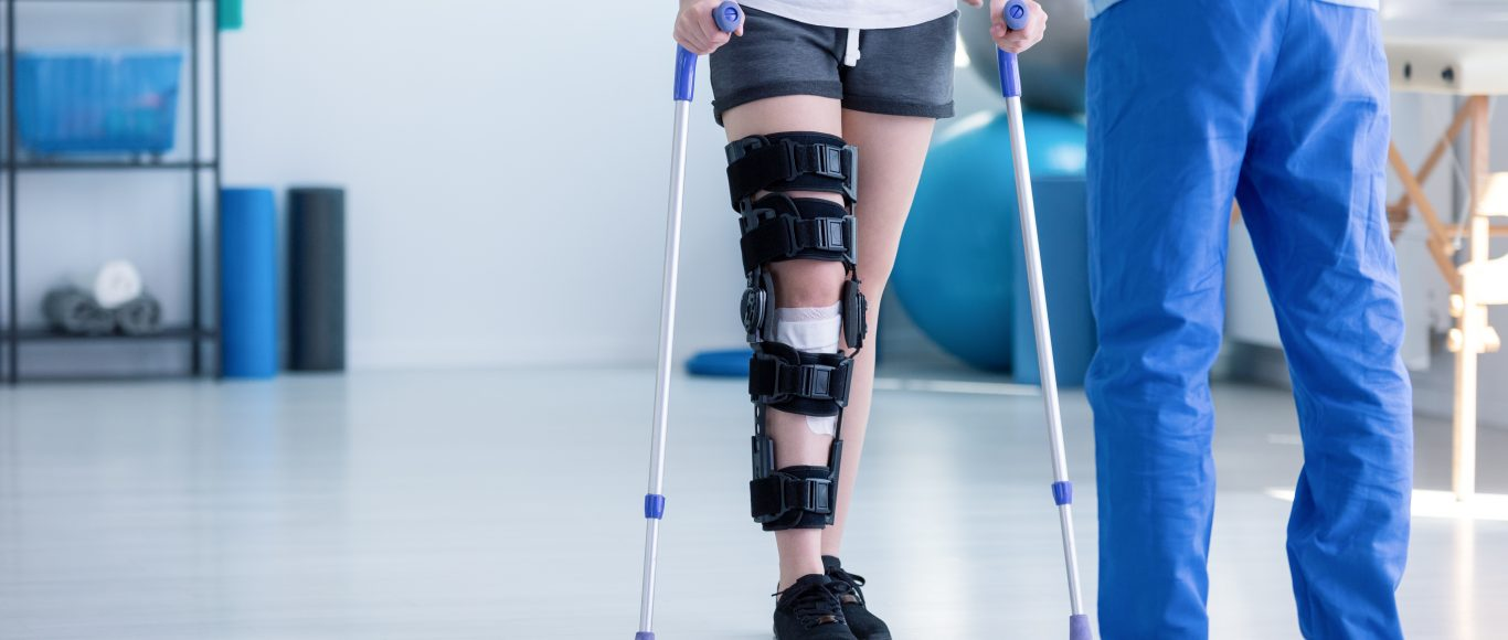 Photo of an orthopaedic practitioner helping someone to walk again