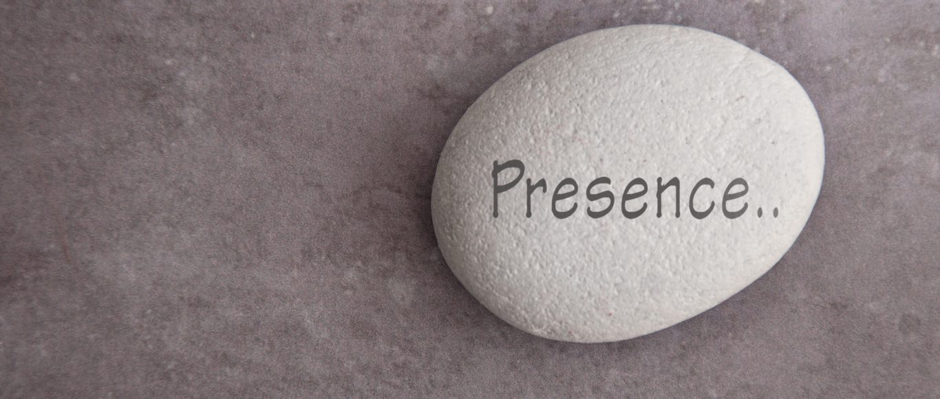 Photo of a pebble with the word 'Presence...' written on it