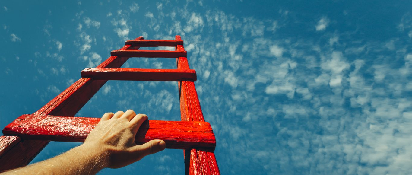 Photo of a hand holding a large red ladder leading up towards the sky