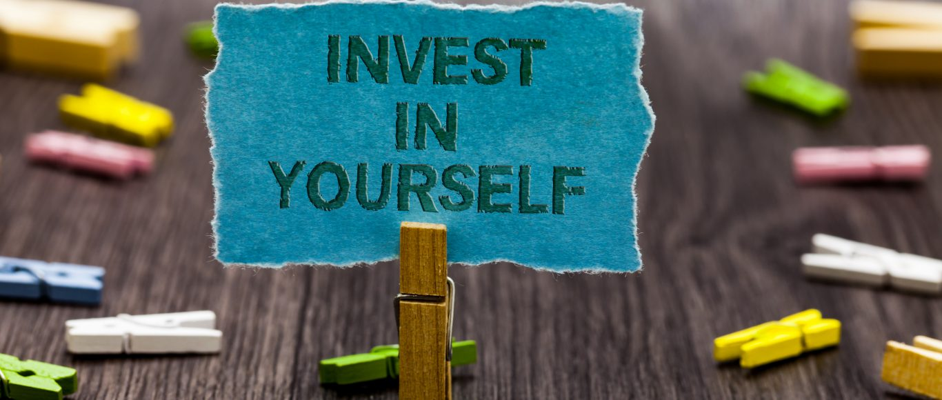 Photo of a peg holding up a small sign saying 'invest in yourself'