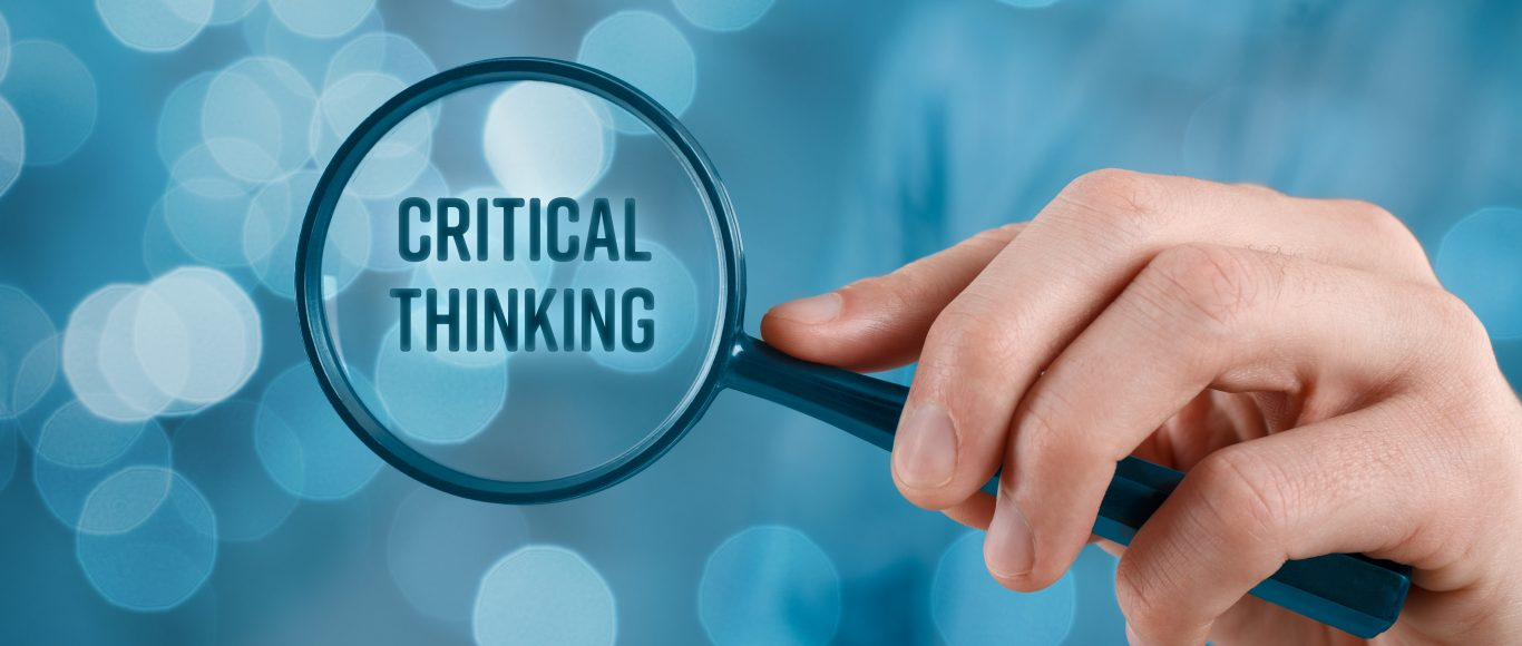 Photo of a magnifying glass over the words 'critical thinking'