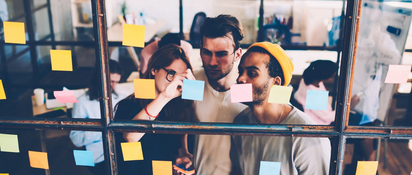 Photo of people looking at post-it notes on a wall