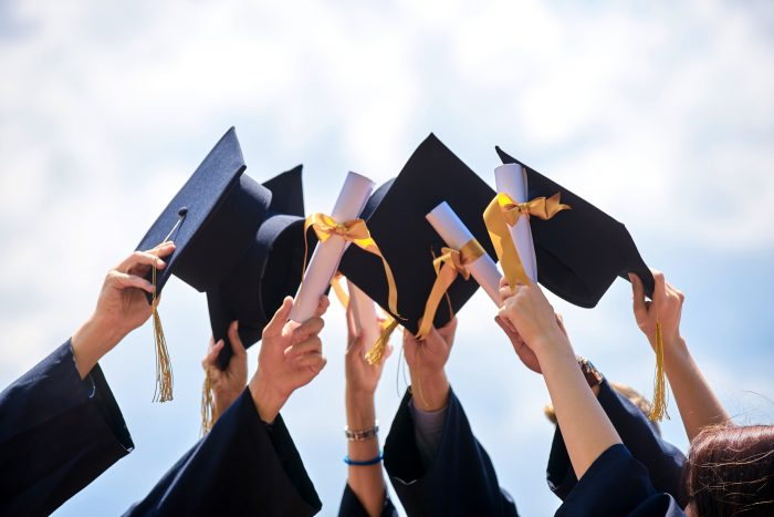 Photo of people holding up their graduation caps