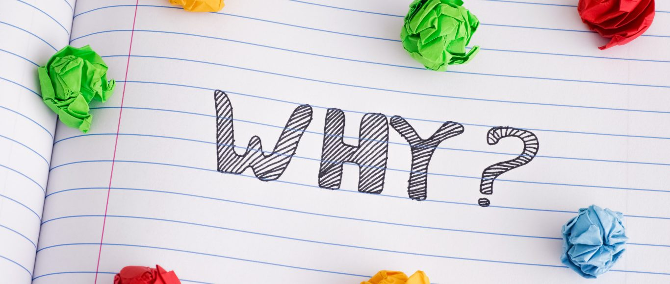 Photo of the word 'WHY?' written in a notepad surrounded by bits of coloured scrunched up paper