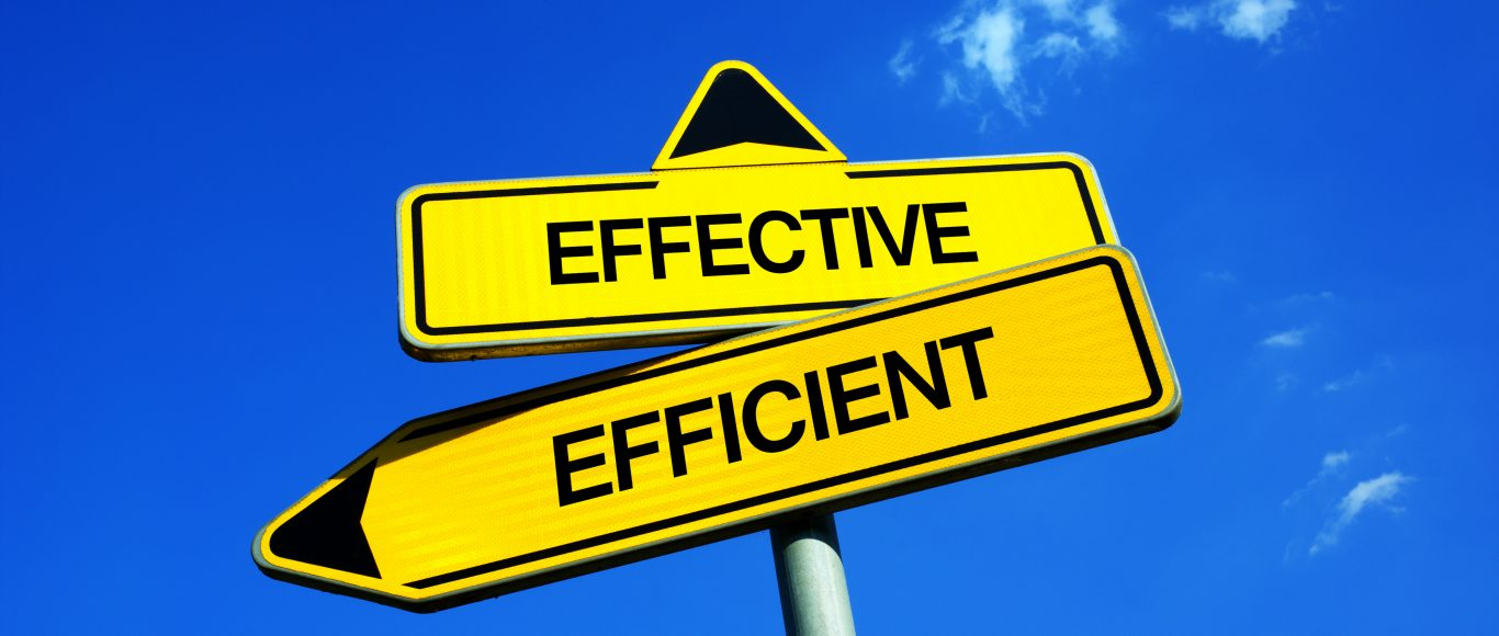 Photo of a sign that says 'Effective' and 'Efficient', pointing in different directions