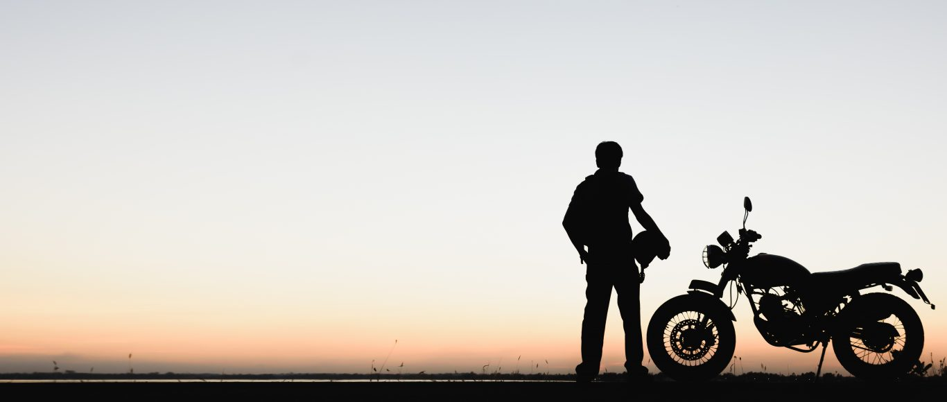Photo of a silhouette of someone stood next to their motorbike