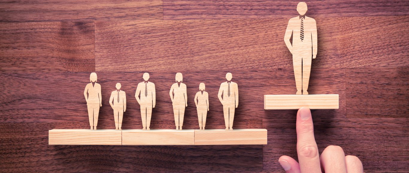 Photo of wooden people with one higher than the others, representing the leader