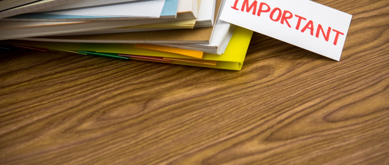 Photo of notebooks stacked up, with a piece of paper saying 'IMPORTANT' pertruding
