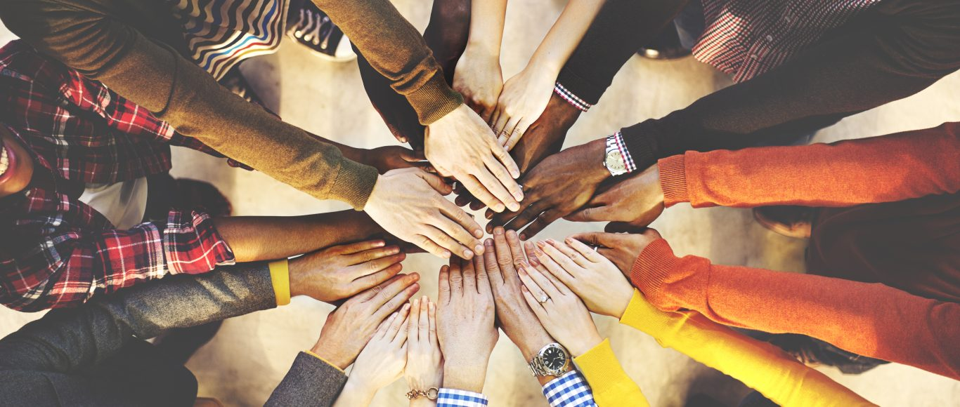 Photo of a group of people putting their hands together