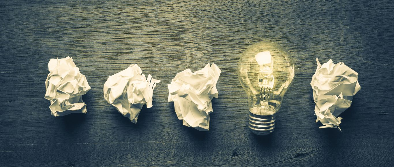 Photo of 4 scrunched up pieces of paper and a lightbulb