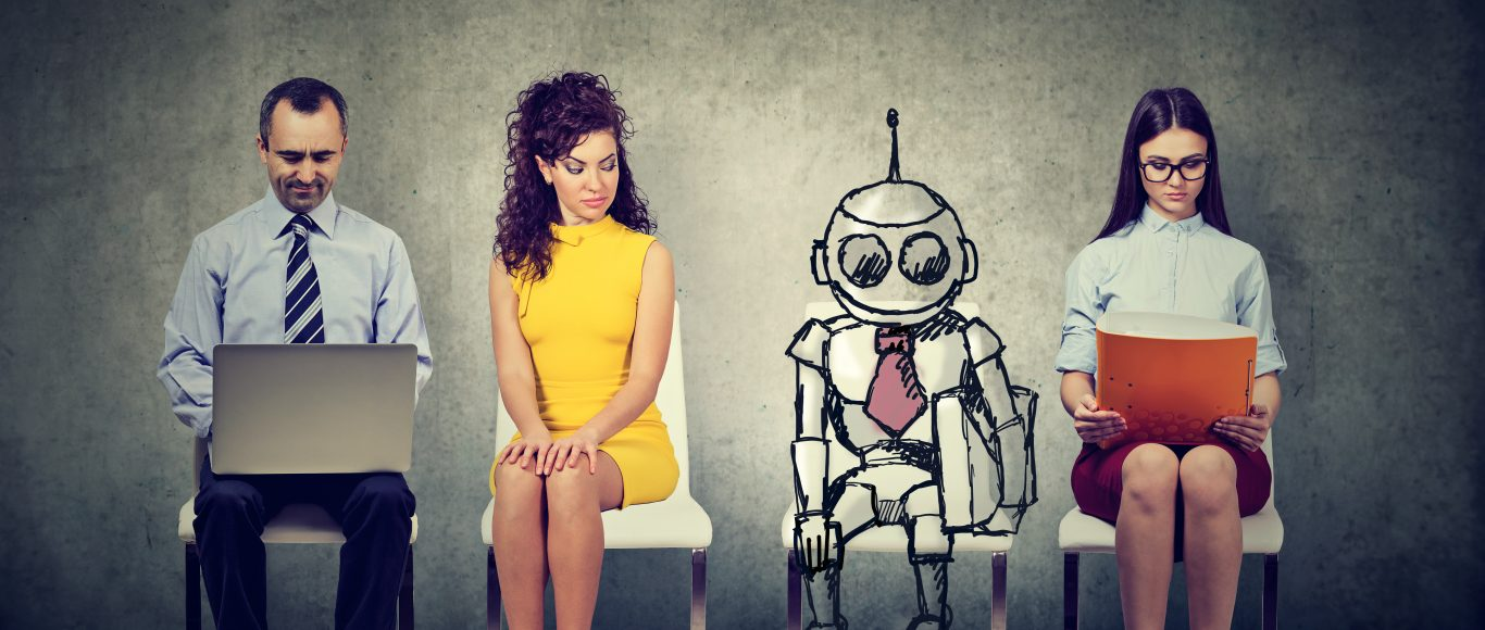 Photo of a robot sat amongst other people at a job interview