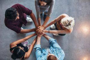 Photo of a team of people putting their hands together in a circle