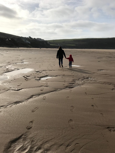 Photo of father and son walking along the beach holding hands