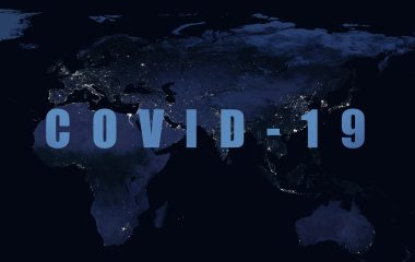 Photo of 'Covid-19' in writing in front of a map of the world