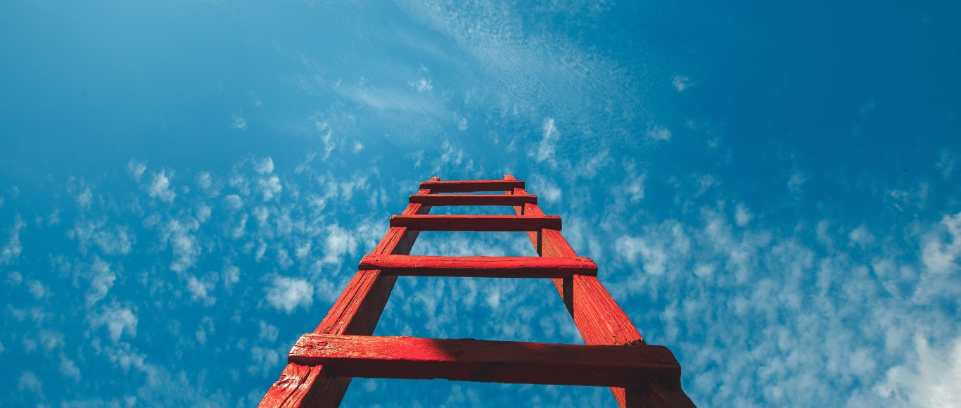 Photo of red ladder going upwards in a blue sky