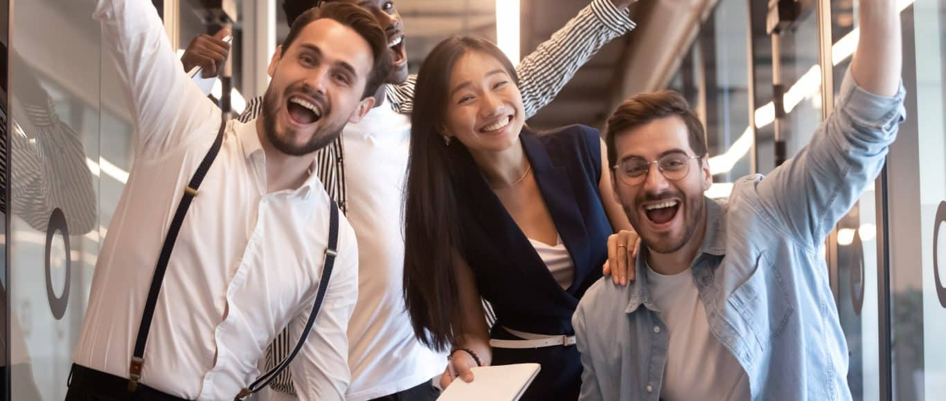 Excited funny multiethnic staff people business team stand in office looking at camera