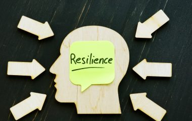 Photo of a head with the word resilience written on a post it note