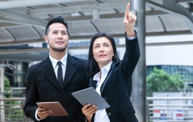 Photo of a man and a women who is pointing towards something, both holding ipads