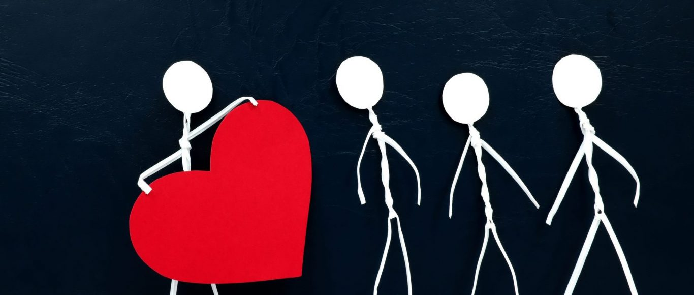 Photo of four stick men, one holding a big heart
