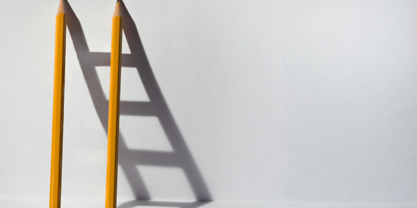 Photo of two pencils leaning against a wall creating a ladder shaped shadow