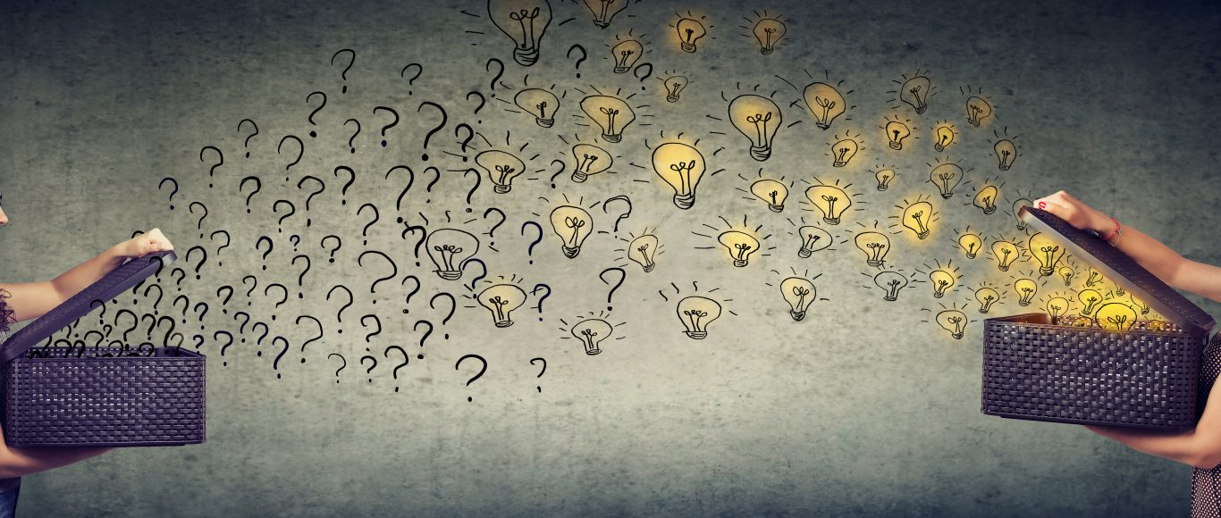 Photo of two girls stood opposite each other holding boxes, one with light bulbs flying out and the other with question marks