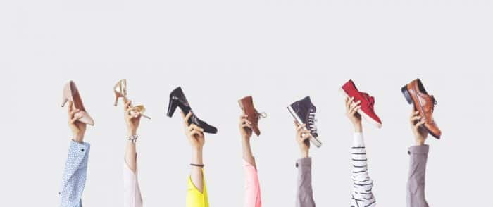 hands holding different styles of shoe