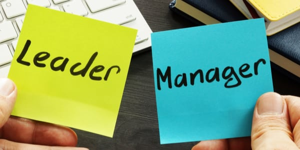 Photo of two post-it notes one saying leader the other manager