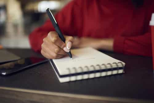 Close up of person writing in a notebook