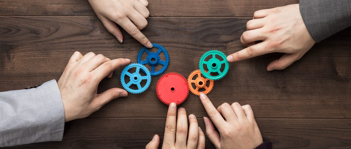 Photo of people each placing a different coloured cog on a table