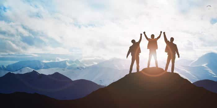 Photo of three people standing on a mountain holding their hands up