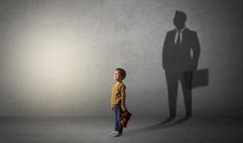 Photo of a little boy imagine that he will be businessman and illustrating his future in a big shadow