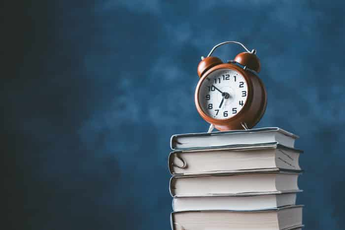 Photo of a clock on top of some books