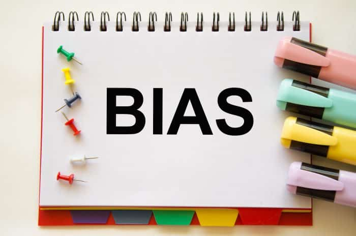Photo of the word 'BIAS' on a notepad next to some pins and highlighters