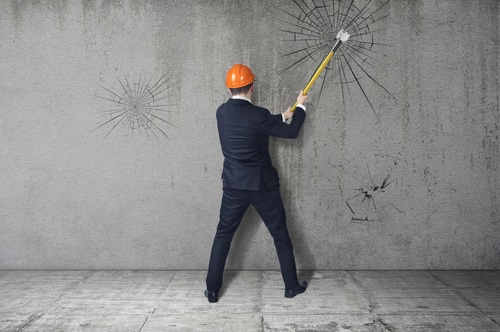 Photo of man in suit and helmet hammer smashes a barrier. The notion of breaking down barriers and achieve goals.