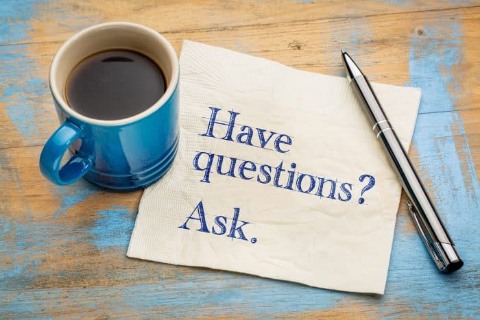 Photo of ' Have questions? Ask.' written on a napkin next to a cup of coffee