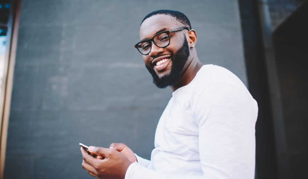 photo of smiling man using a mobile